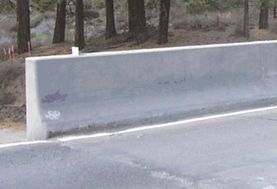 A familiar concrete barrier, by the side of the road, made with cement.