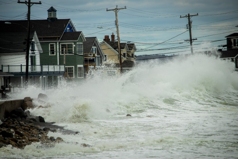 A wave crashing into the shore in front of a row of houses